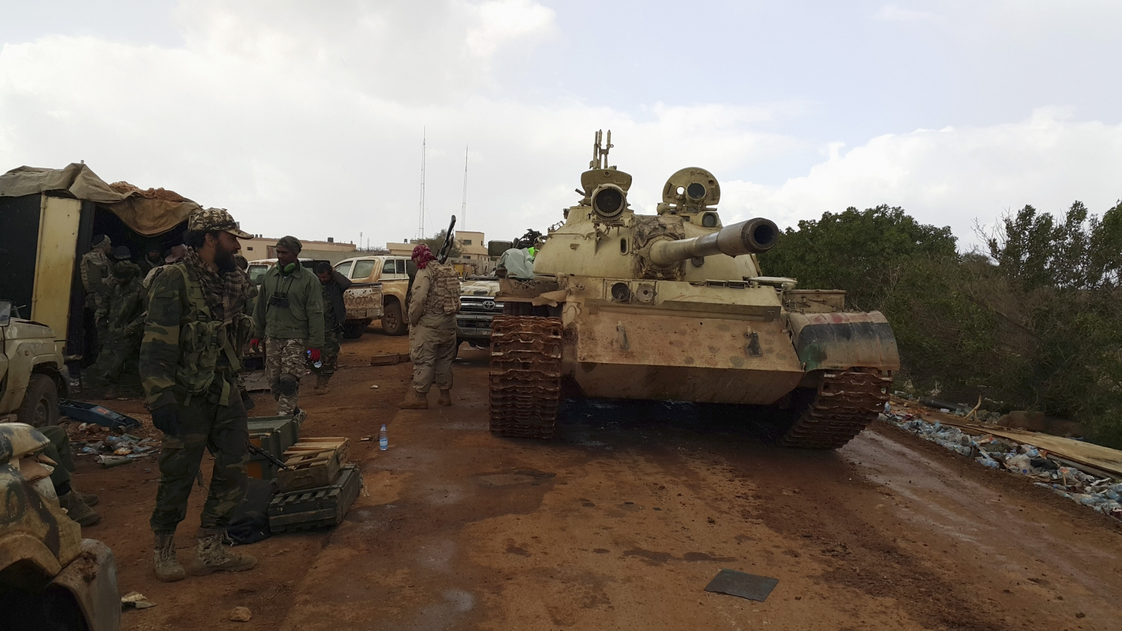 Members of Libyan pro-government forces, backed by locals, stand beside a tank at a rally point during nearby clashes with the Shura Council of Libyan Revolutionaries, an alliance of former anti-Gaddafi rebels who have joined forces with Islamist group An