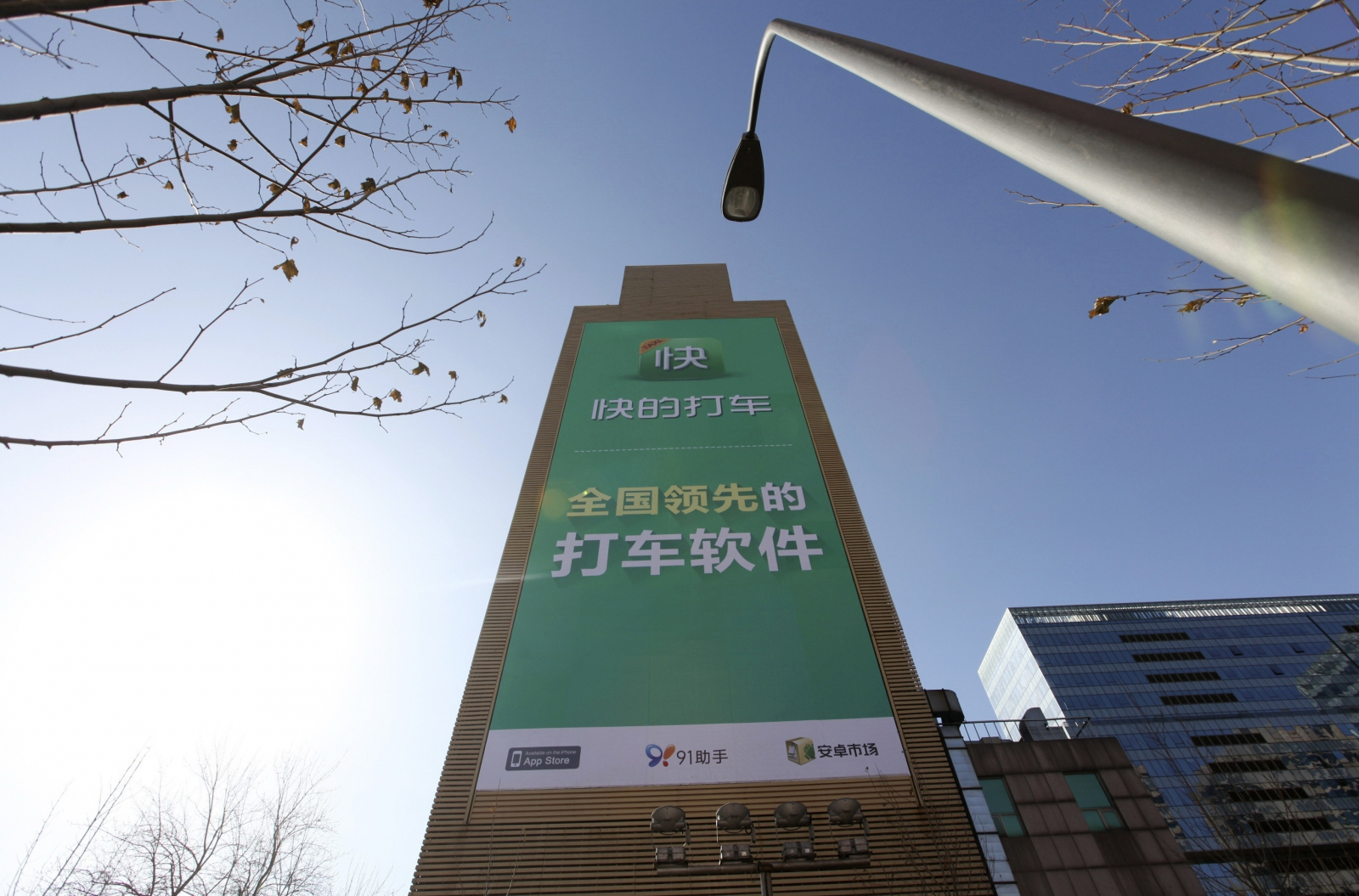 """n advertisement of """"Kuaidi Dache"""" taxi-hailing application is seen on the exterior of a building in Beijing."""