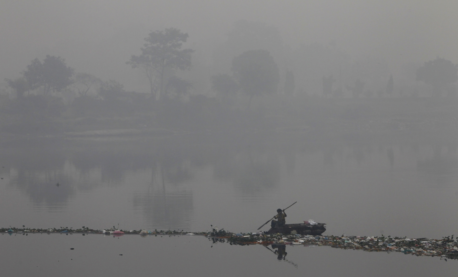 A rag picker collects recyclable materials in the polluted waters of river Yamuna amid dense smog in Delhi.