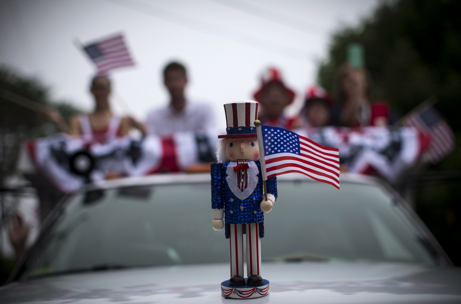 An Uncle Sam figure sits on the hood of a car in a July Fourth parade in the village of Barnstable, Massachusetts