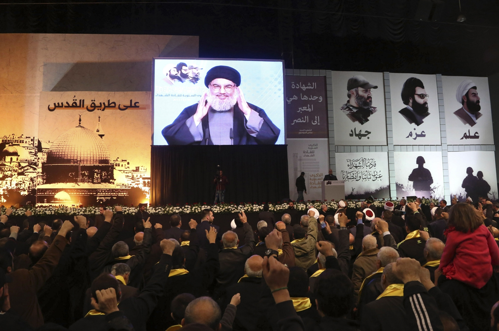Lebanon's Hezbollah leader Sayyed Hassan Nasrallah greets his supporters through a giant screen during a rally commemorating the annual Hezbollah Martyrs' Leader Day in Beirut's southern suburbs February 16, 2015