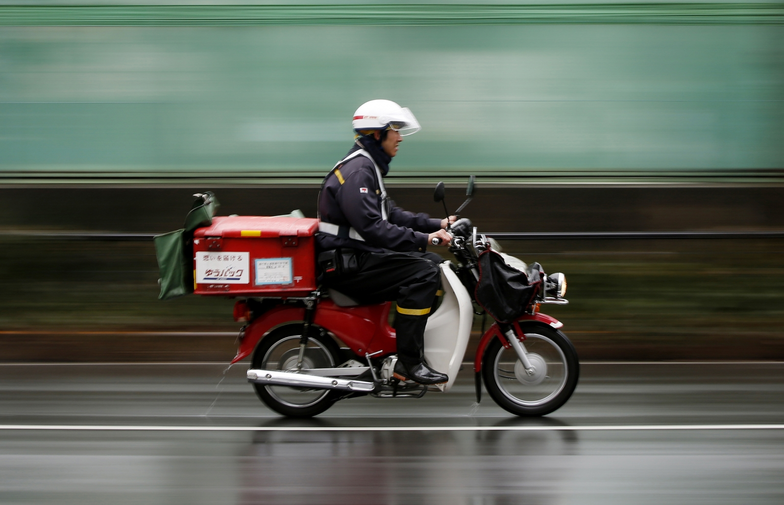A postman of Japan Post rides a motorcycle in Tokyo