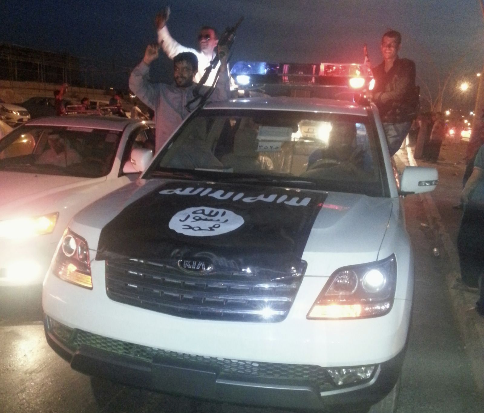 Isis militants in a commandeered police vehicle in Mosul, Iraq (Reuters)
