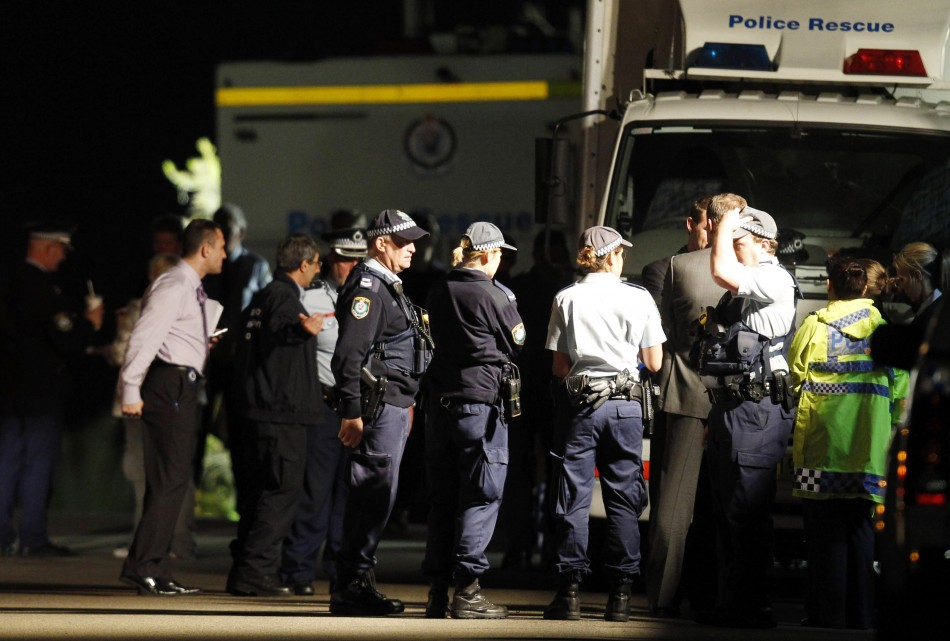 Police and emergency workers stand near a house where bomb squad officers are working in Mosman