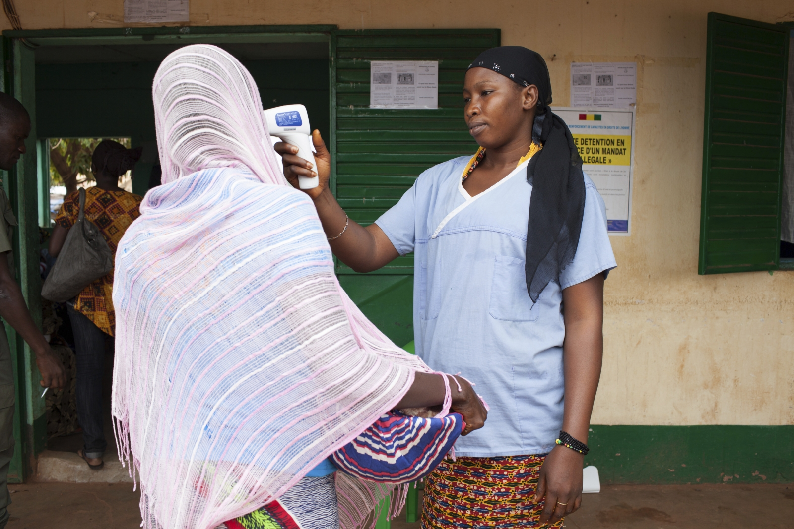 A health worker checks the temperature of a woman leaving Guinea at the border with Mali in Kouremale,
