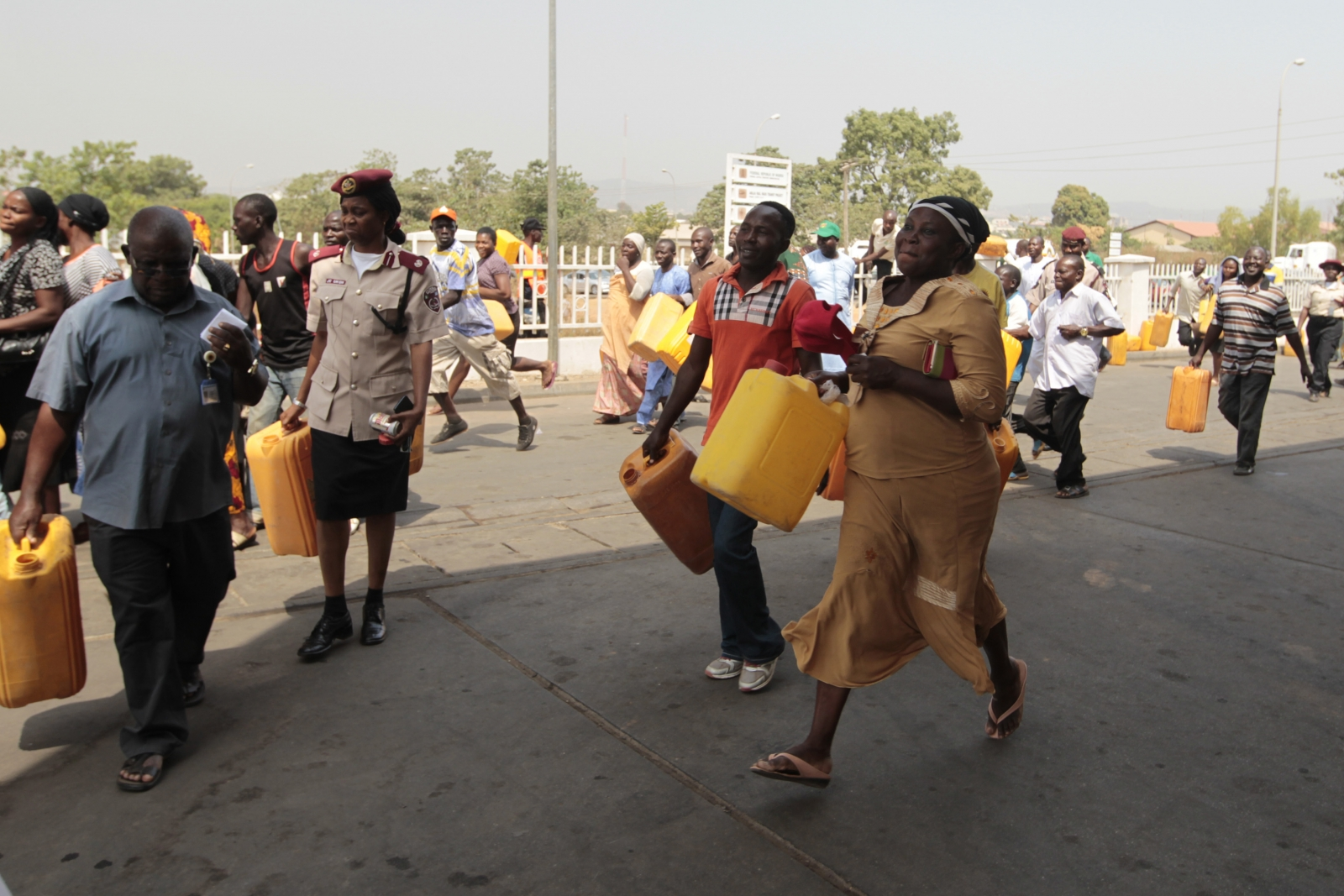 People run toward kerosene cooking fuel pumps during the launch of the