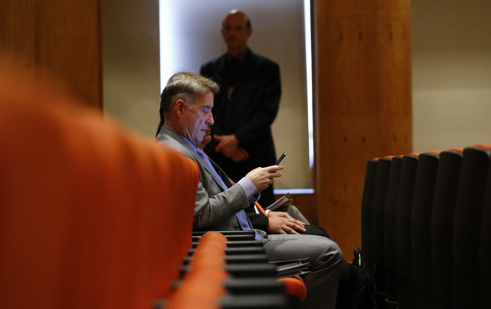 Brazilian tycoon Eike Batista checks his mobile phone before his court hearing in Rio de Janeiro November 18, 2014.