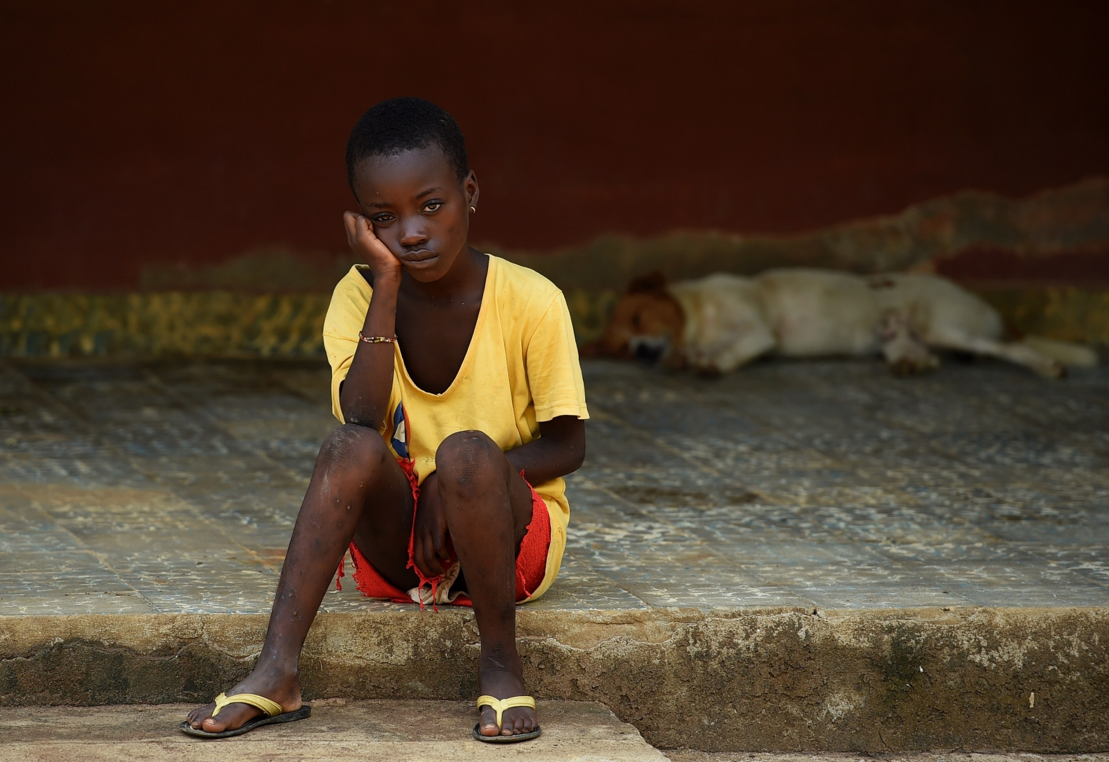 A child under quarantine sits outside a care center in Lokomasama, in the Port Loko province which has been severelly hit by the Ebola.