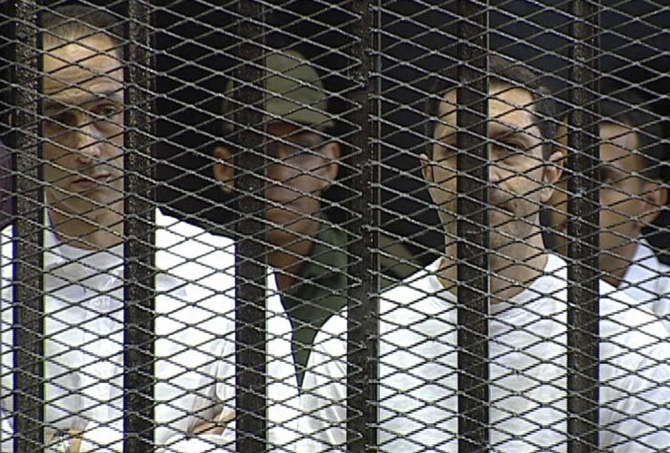 Alaa and Gamal Mubarak stand in the courtroom during their trial at the Police Academy in Cairo