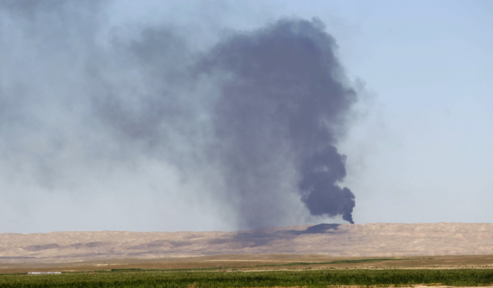Smoke rises from the Ajil oil field