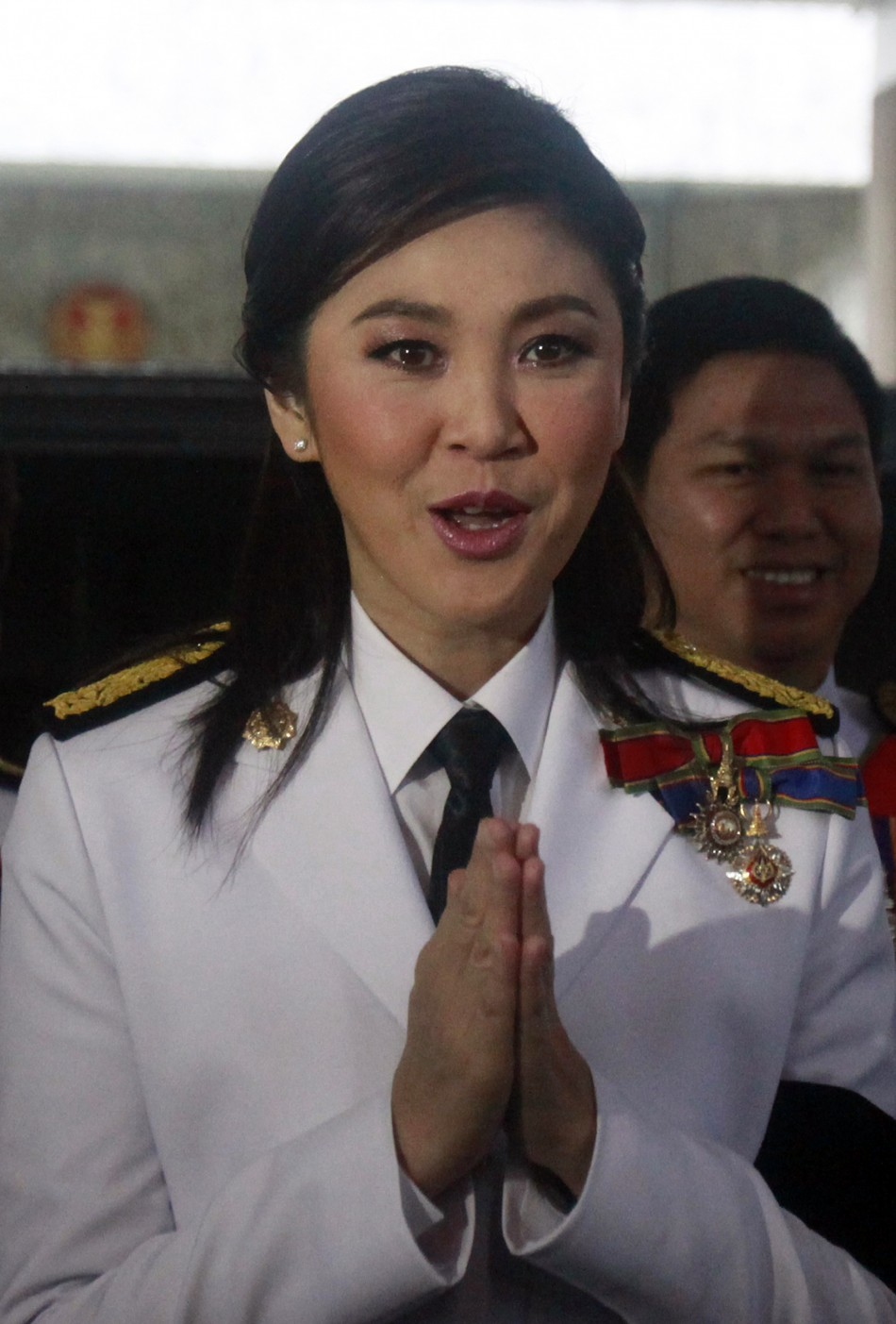Prime Minister elect Yingluck Shinawatra of the Puea Thai Party gestures to media as she arrives at the parliament before the inauguration ceremony of the National Legislative Assembly in Bangkok