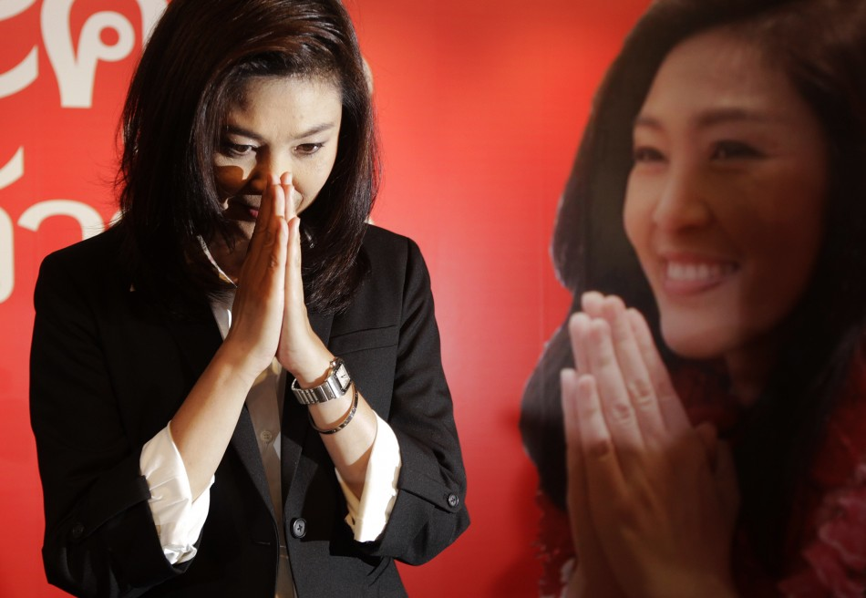Yingluck Shinawatra greets reporters and supporters gathered at her partys headquarters after voting in general elections ended in Bangkok