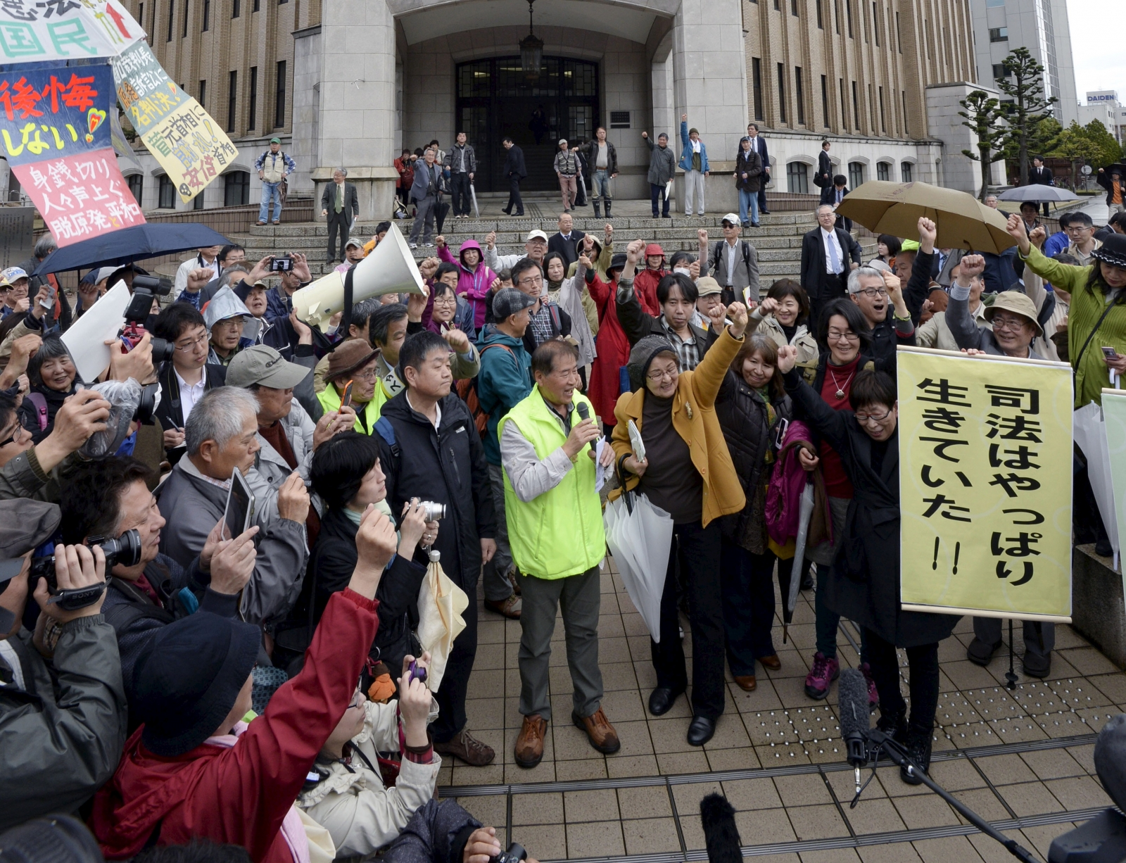 Anti-nuclear protesters cheer outside Fukui District Court