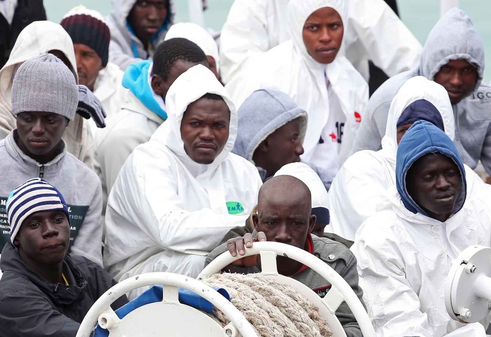 Migrants wait to disembark in Catania