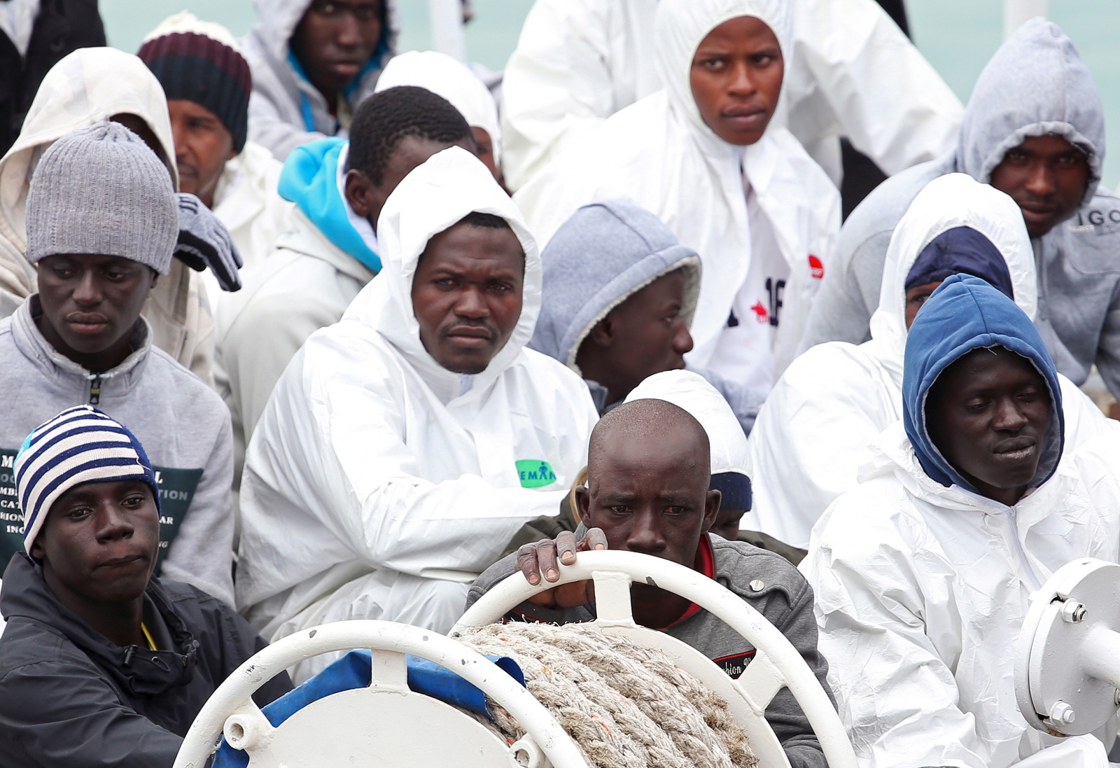 Migrants wait to disembark in Catania