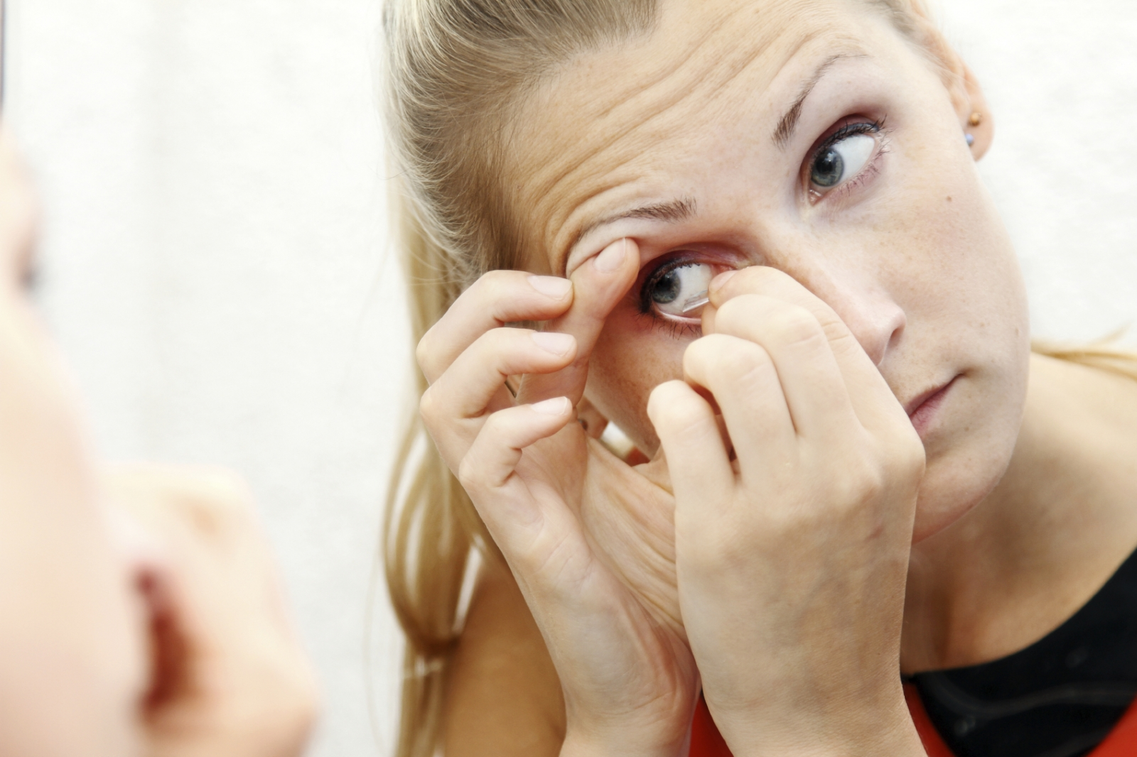 A woman struggles to apply contact lenses