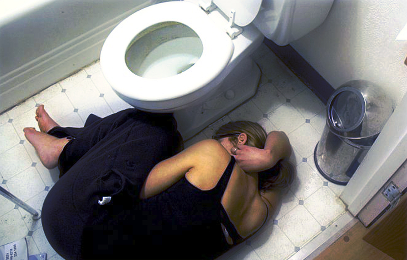 Woman lying bathroom floor pain