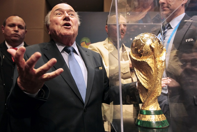 Sepp Blatter gestures World Cup trophy