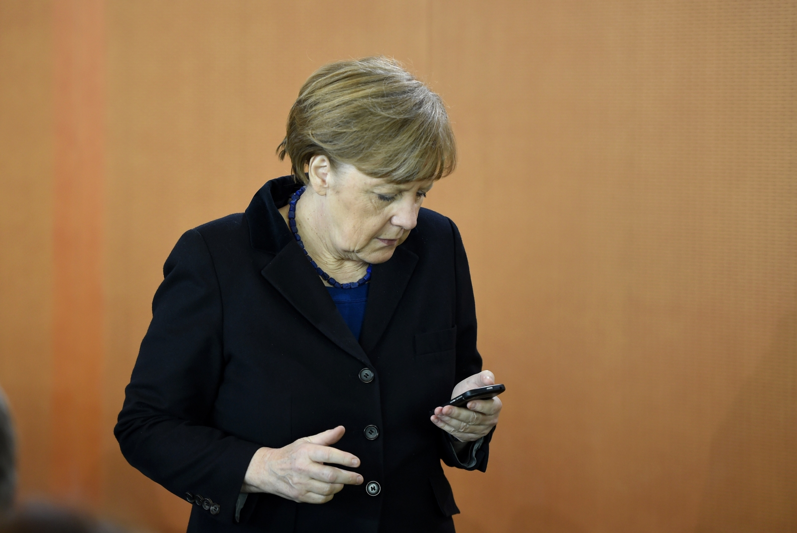 Angela Merkel looking at her phone