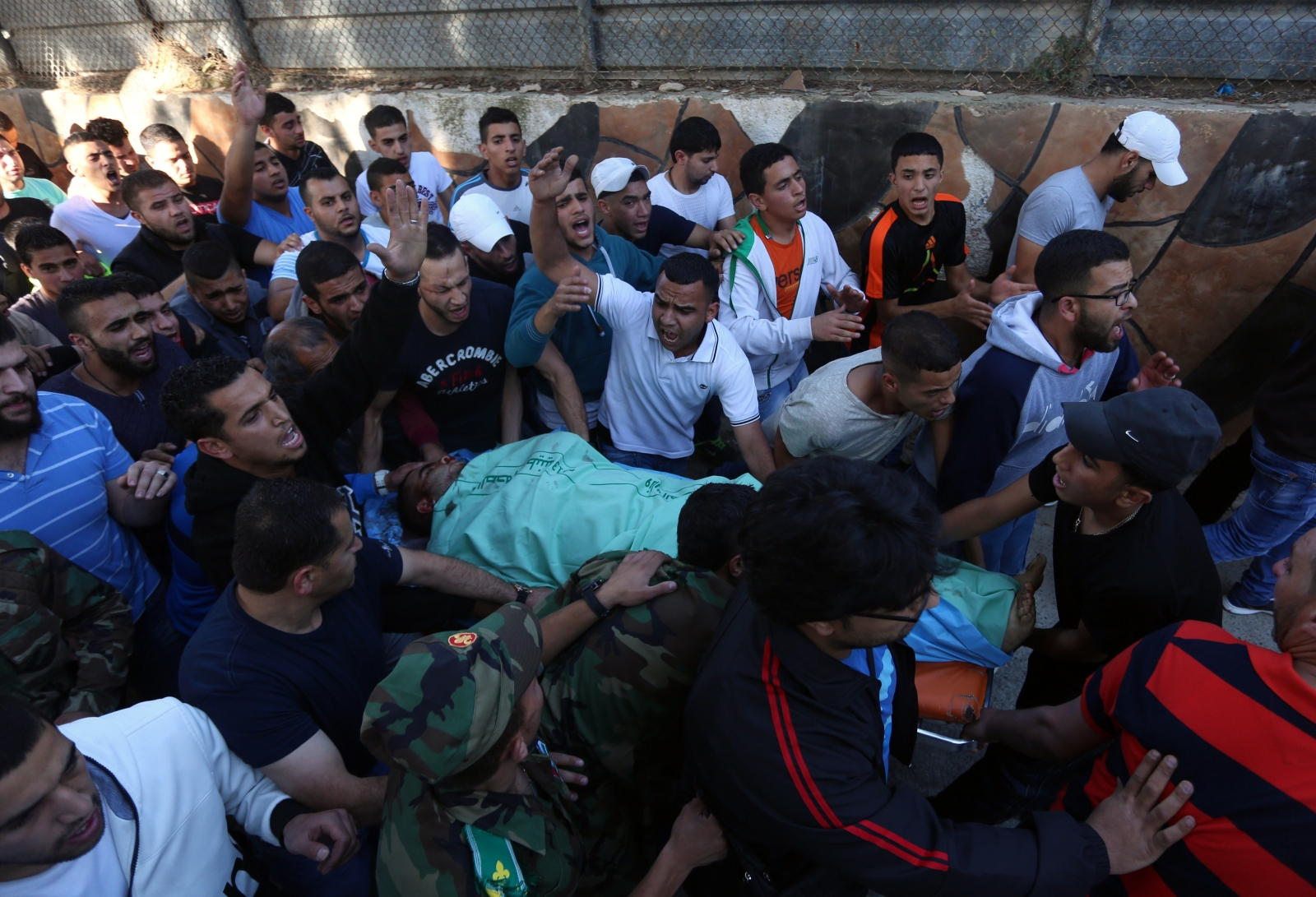 Palestinians carry the body of