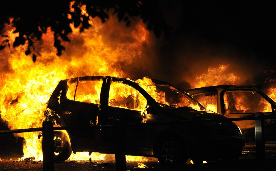 Cars burn on a street in Ealing, London