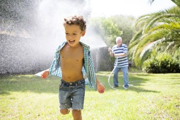 Child playing in sprinklers