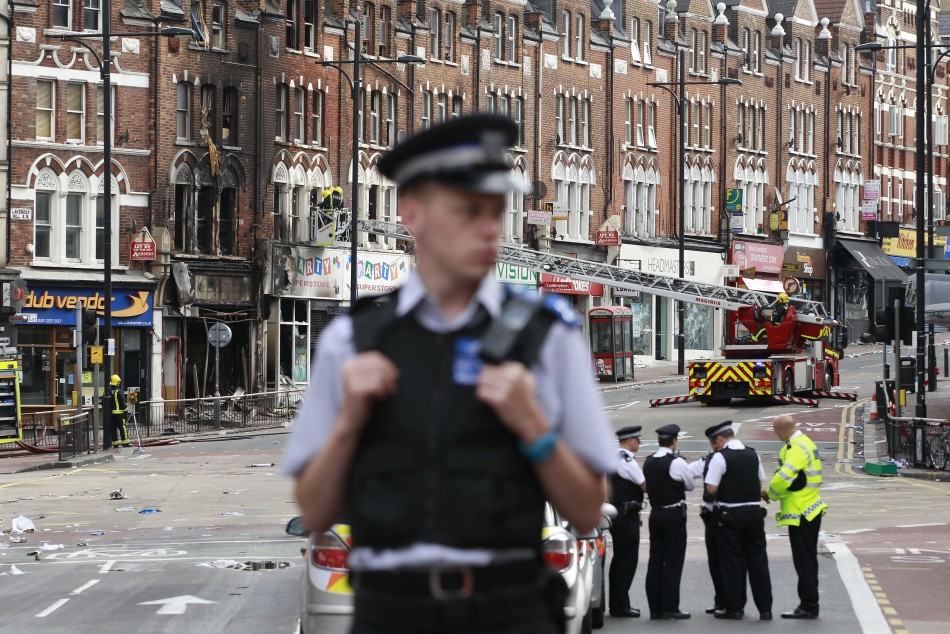 Police officers stand near a burnt out shop in Clapham Junction, in south London