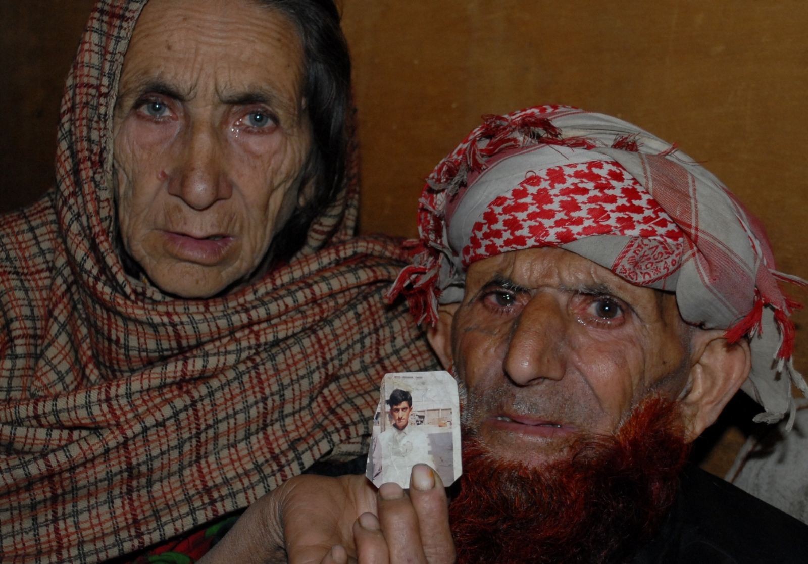Shafqat Hussai's parents hold up his photo