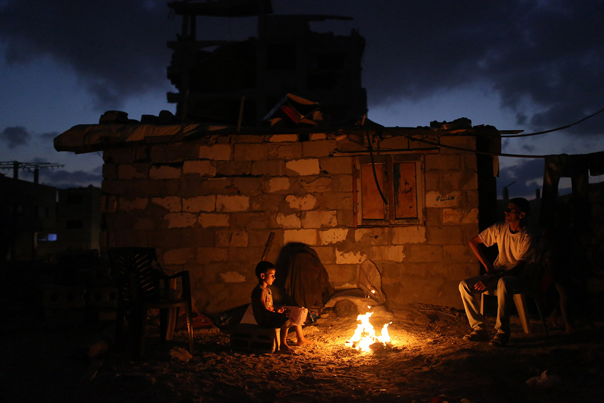 gaza power cuts residents living out electricity for up to  a palestinian family sits around a fire next to their home in al tufah in the east of gaza city during a power outage on 27 2015 mahmud hams afp