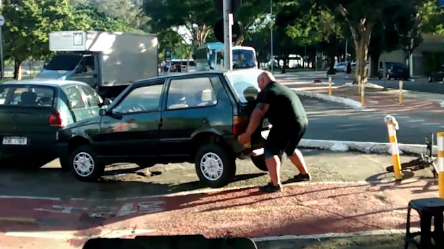 man lifts car