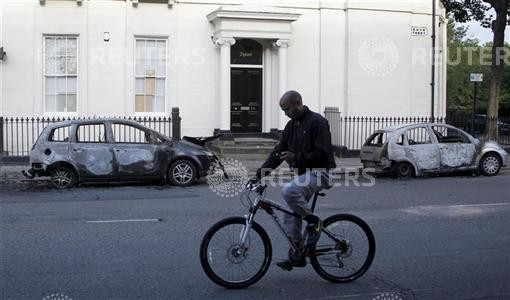 A man looks at his mobile phone as he cycles past two burned out cars in the Toxteth area of Liverpool