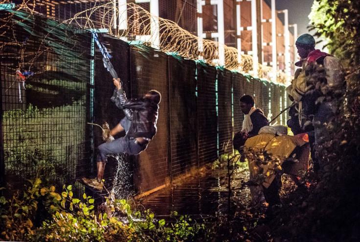 A migrant climbs a security