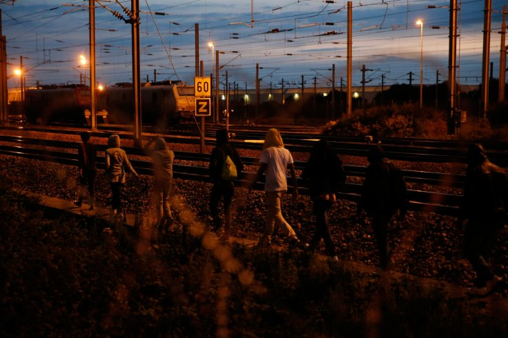 Migrants walk along the tracks