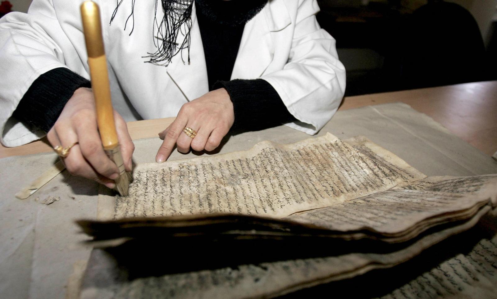 An expert restores a manuscript at BaghdadNationalLibrary