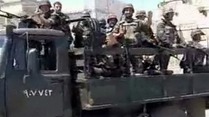 Army trucks carrying soldiers enter into city