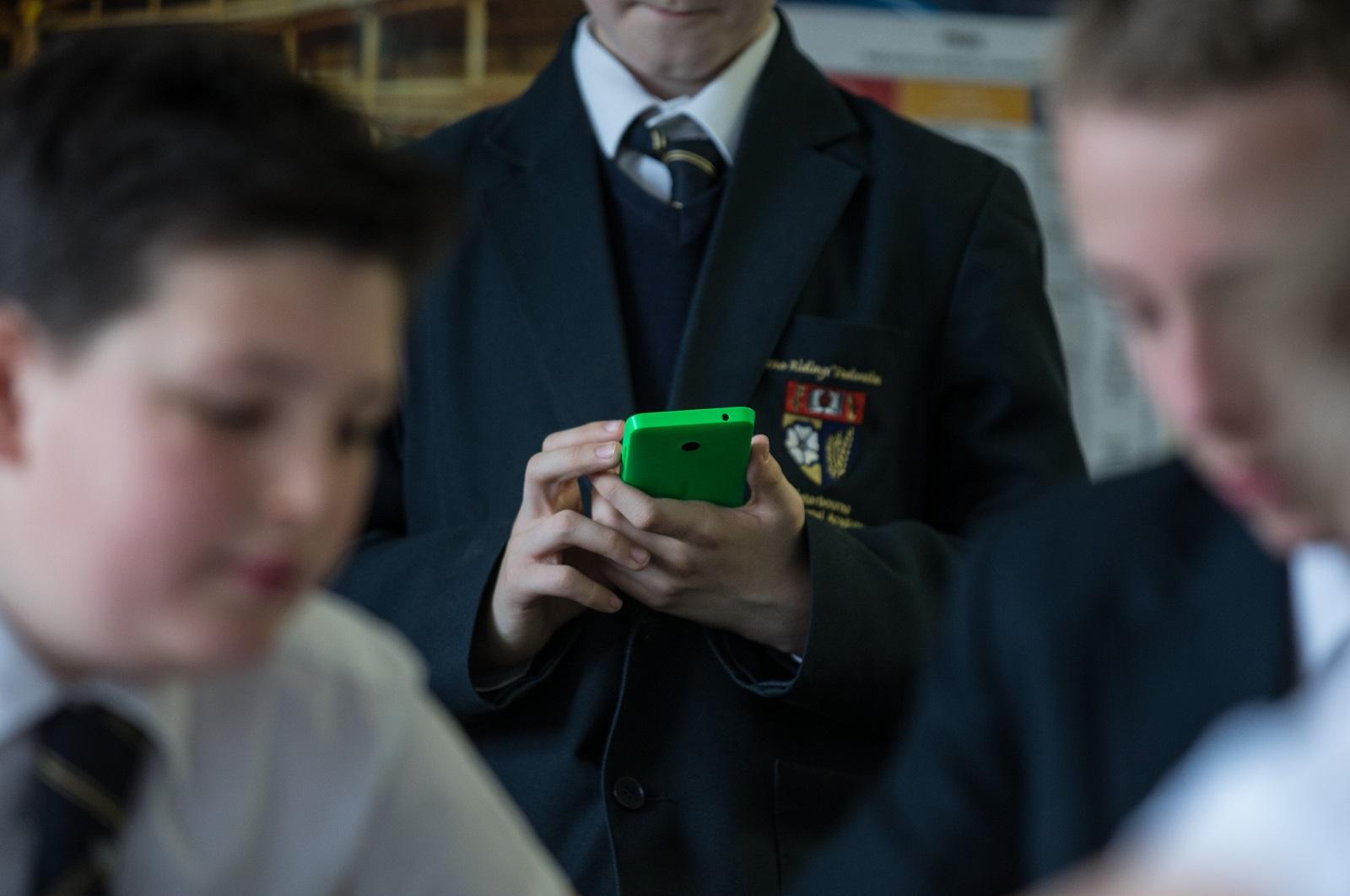 UK schoolboy using smartphone