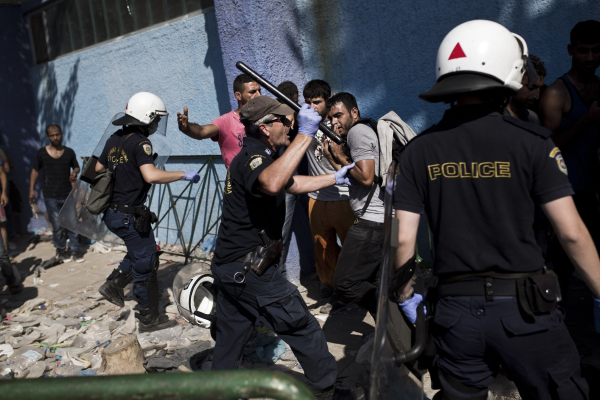 Policemen try to disperse migrants