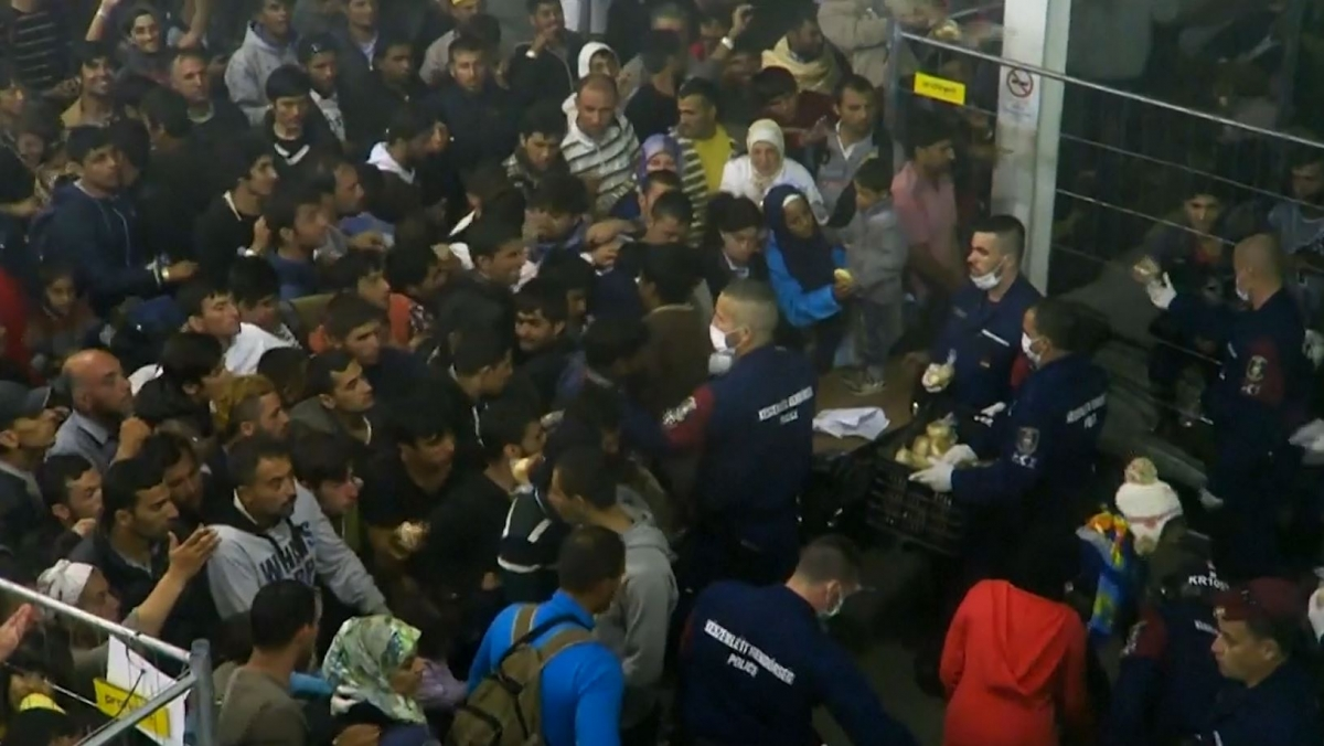 Hungarian police throws food at migrants
