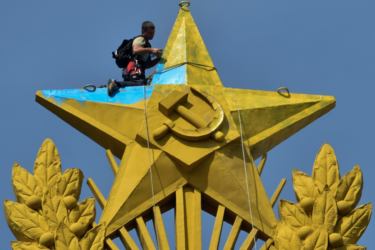 A worker repairs a Soviet star