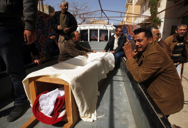 Relative cries next to a coffin