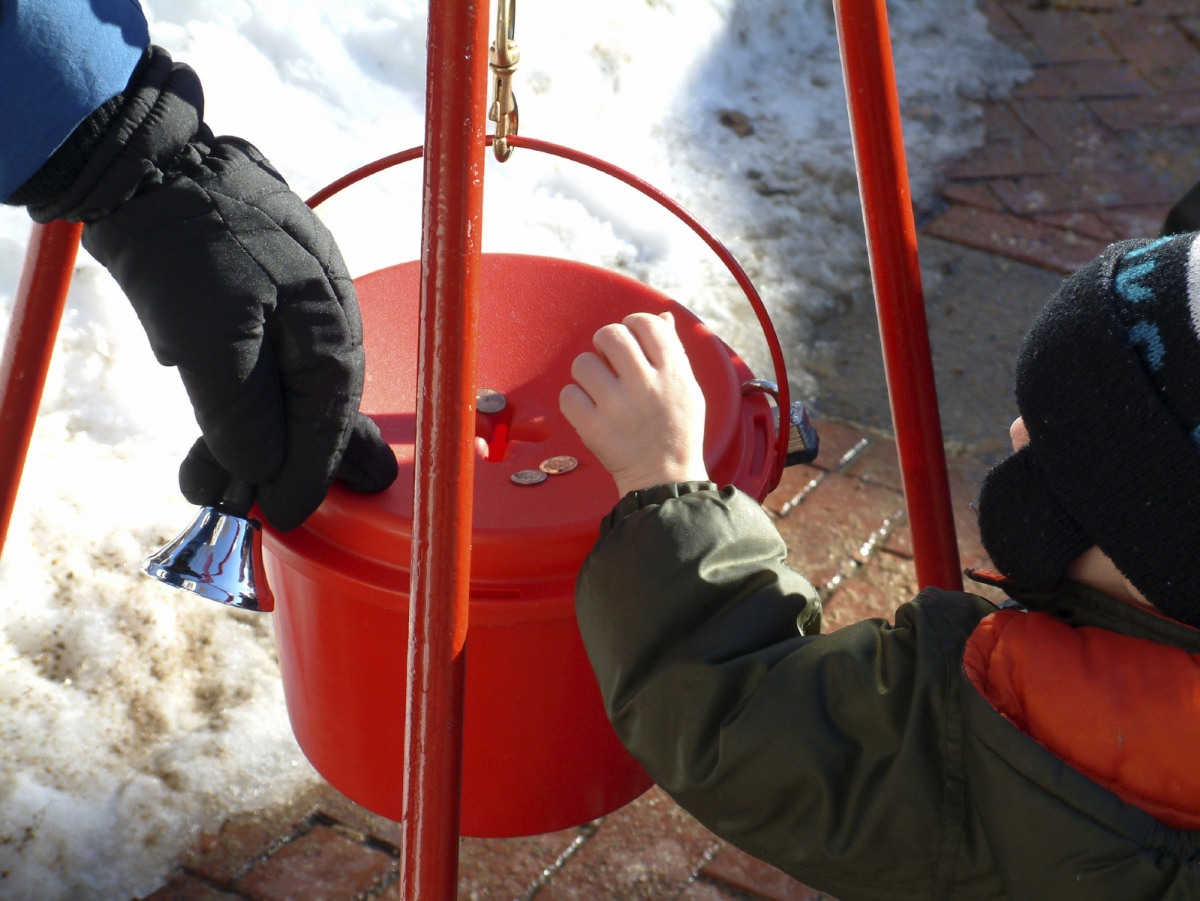 Young child puts coins in charity box