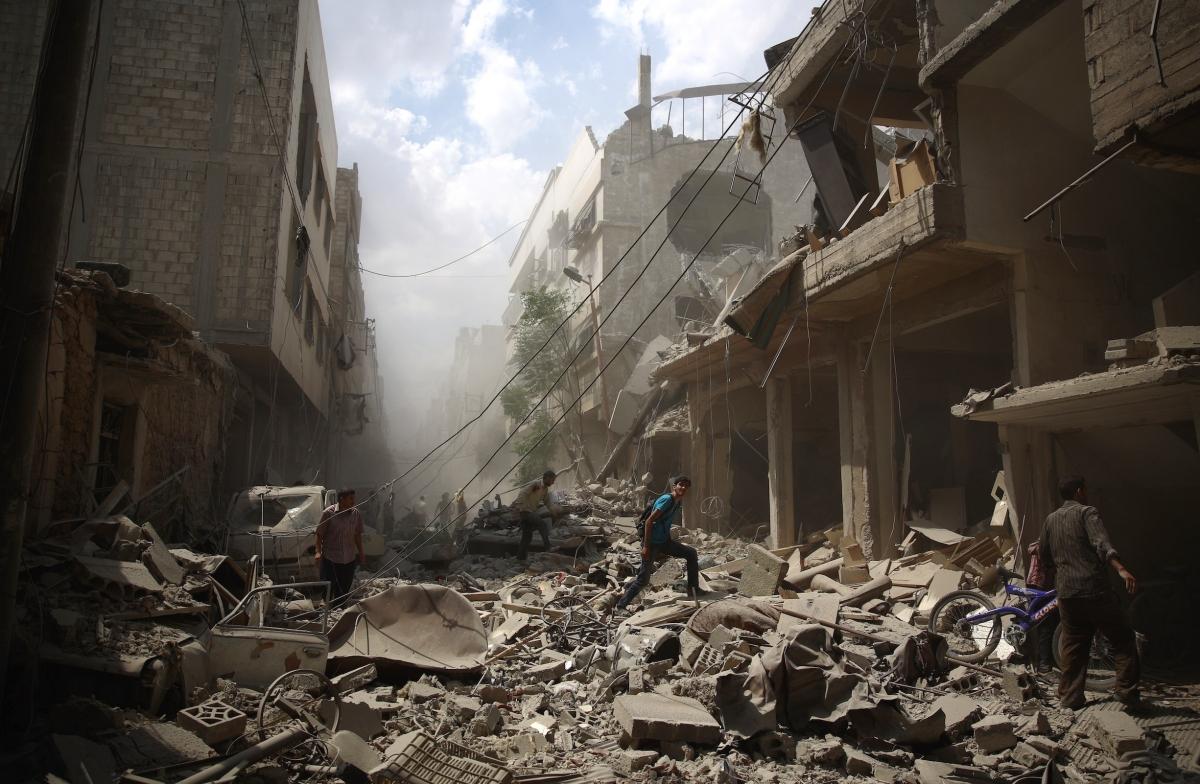 Syrians walk amid the rubble