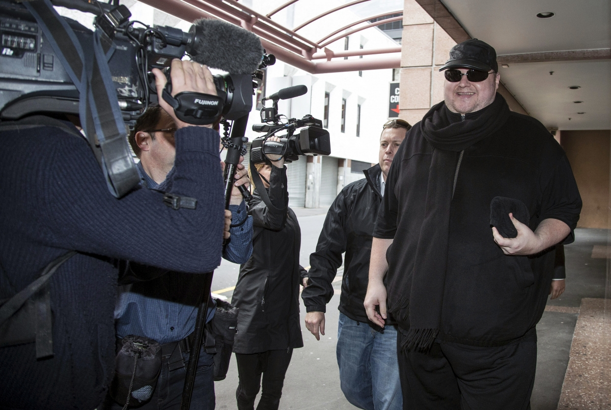 Kim Dotcom smiles at news cameras