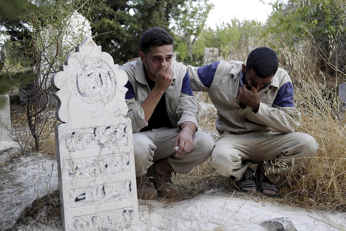Membri della Protezione Civile Siriana piangono un loro compagno ucciso in un raid russo su Eshim (Idlib). Credit to: Khalil Ashawi/Reuters