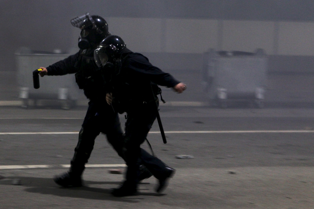 A policeman helps an injured colleague during clashes with protesters in Kosovo's capital Pristina October 12, 2015.