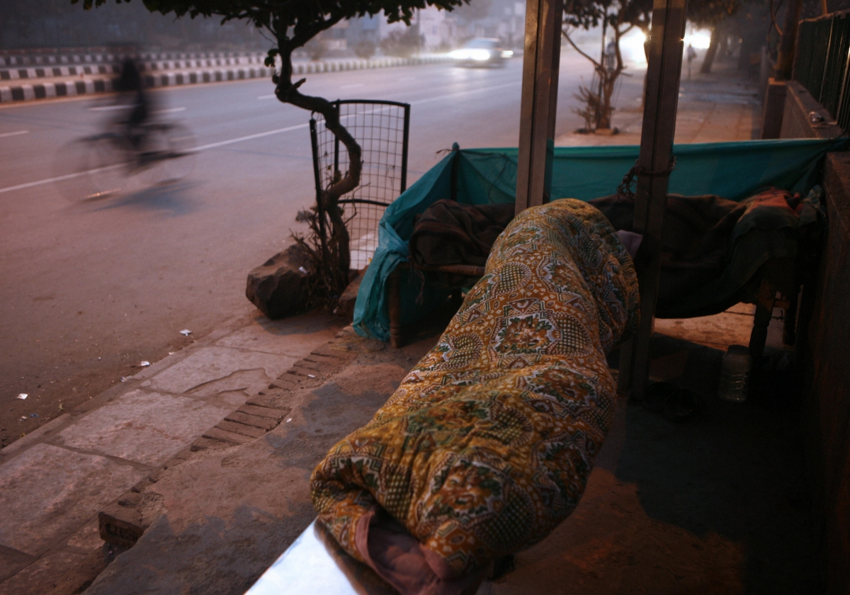 Homeless Indian man at bus stop