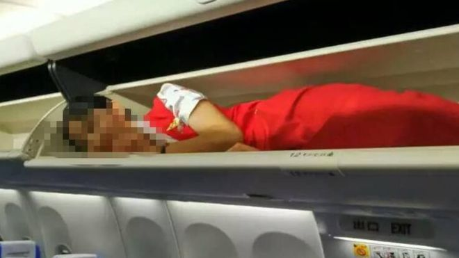 Kunming Airlines crew members overhead lockers China