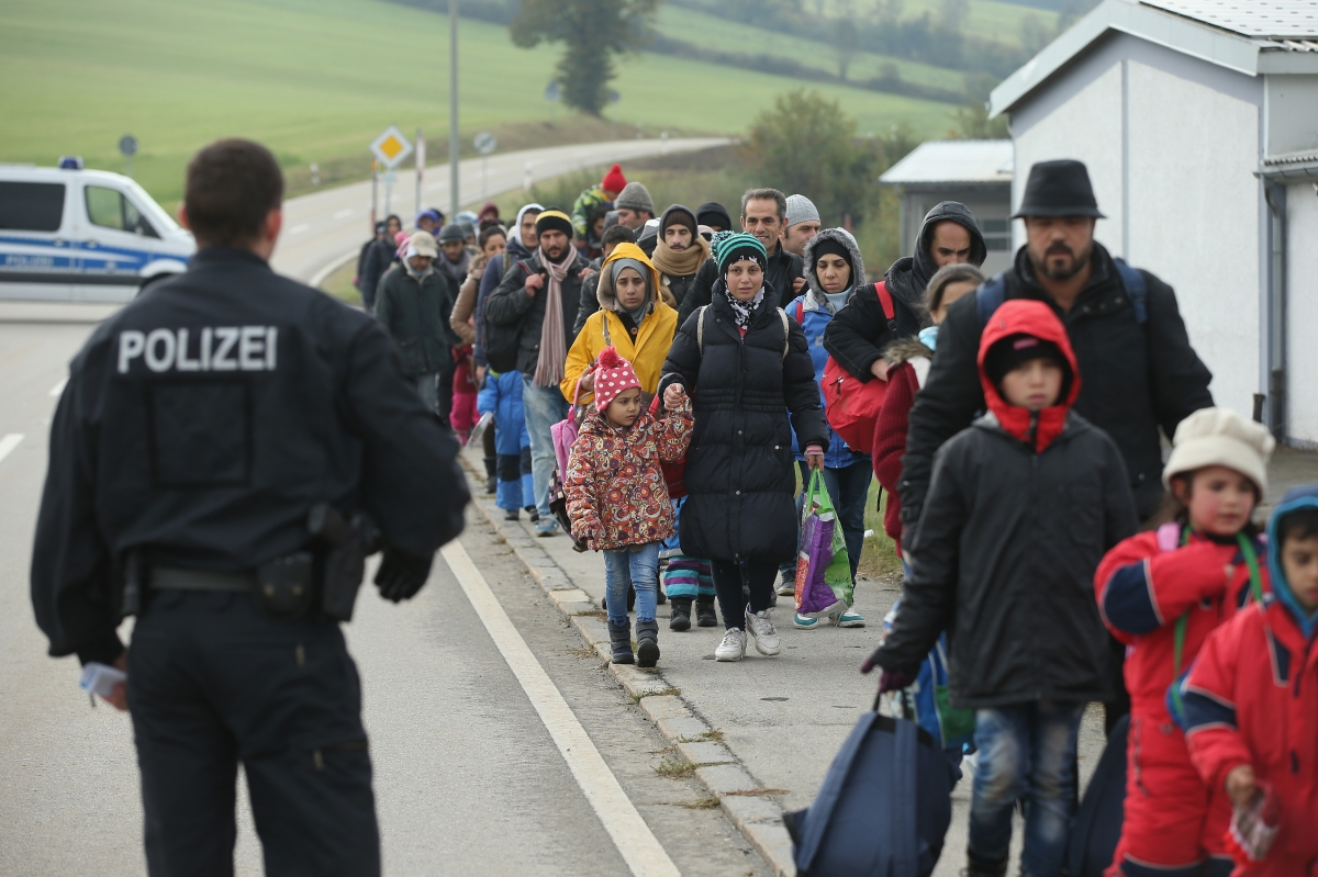 A German policeman directs migrants who had walked across the nearby border from Austria on October 17, 2015 in Wegscheid, Germany.
