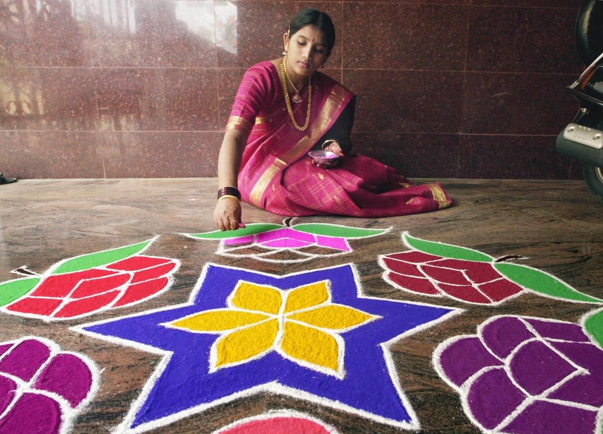 Girl making Rangoli designs in India
