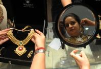 Indian woman tries on gold jewellery